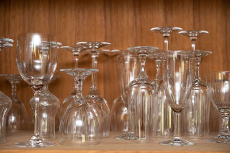 different wine glasses in wooden cabinet