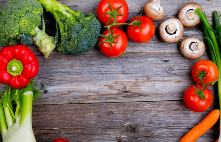 frame of different vegetables on wooden ground