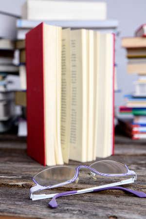 Buch und Lesebrille vor Stapeln verschiedener Bücher auf Holztisch