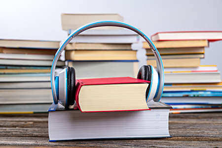 book with headphone in front of piles of different books on wooden table