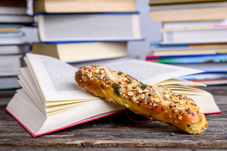 book and little whole grain bread in front of piles of different books on wooden table 版權商用圖片