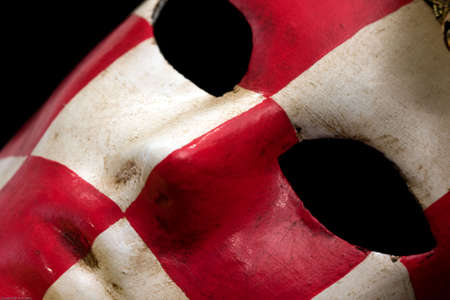 Red & white checkered carnival mask black background close-up