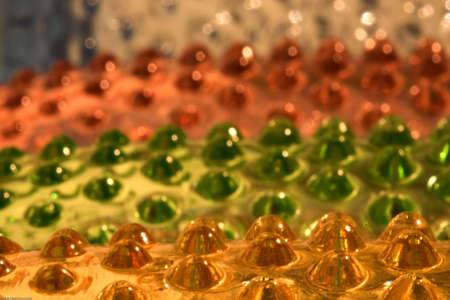 Close-up of bright orange, green, and yellow glass with bumps Stock Photo