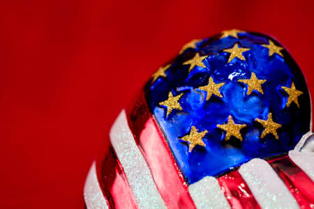 American flag Christmas ornament with red background close-up of stars