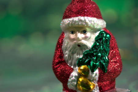 Close-up of a Santa Christmas ornament with green backdrop