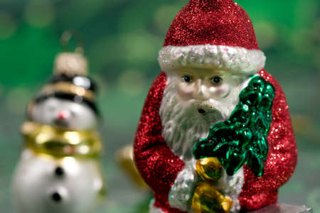 Close-up of a Santa Christmas ornament with a snowman in the background  Stock Photo