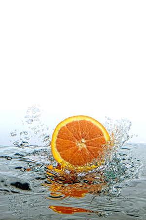 Orange falling into water creating a splash Stock Photo