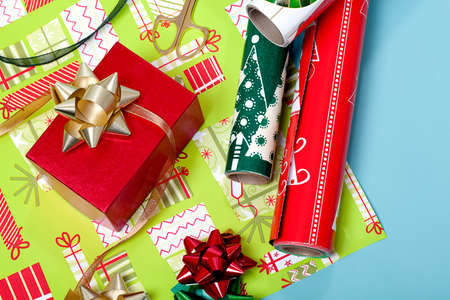 Red box with a gold bow and wrapping paper in the background Stock Photo - 11092541