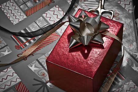 Red box with bow and wrapping paper in the background