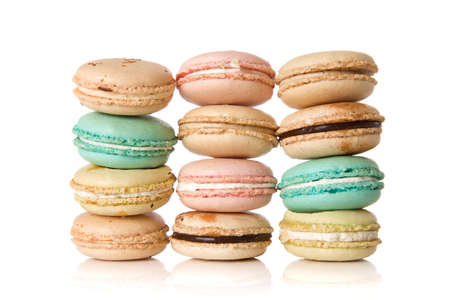 Stacks of assorted delicious macaroons against a white background