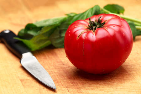 Ripe Tomato Ready To Cut With Fresh Basil On Cutting Board Stock Photo - 22285732