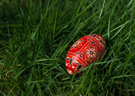 Colorful and beautifully designed egg in the grass