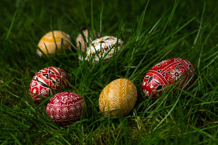 Colorful and beautifully designed eggs in the grass