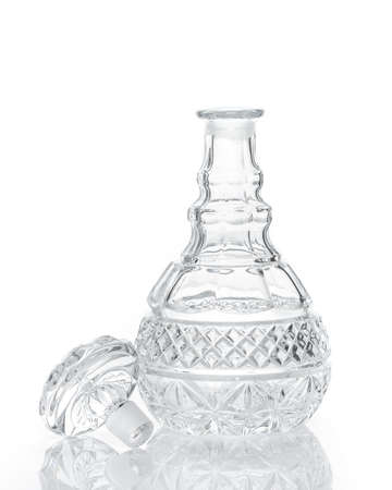 Cut crystal whiskey decanter and stopper isolated on white with reflection