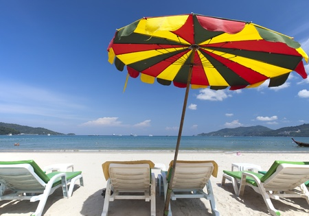 Beach chair and colorful umbrella on the beach in sunny day, Phuket Thailand  photo