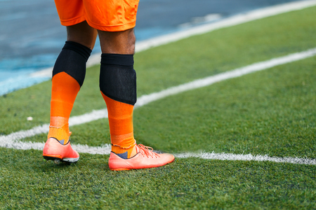 Football playerre in orange suite on conner of yard. Stock Photo