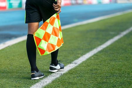 Linesman with flag Standing on football yard.
