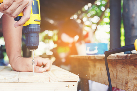 Carpenters screwing a wood plate by wireless drill for make a chair, Diy at Home concept Stock Photo