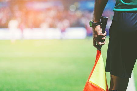 Grensrechter met vlag tussen de wedstrijd van het nachtvoetbalspel.
