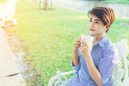 Beautiful short hair woman sitting on a white chair and drinking a favorite beverage in white cup for resting between her outdoor working business in the park. Stock Photo