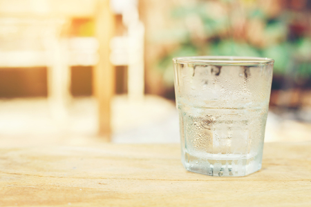 A glass of cold pure water put on the wooden table setting in the garden. Stock Photo