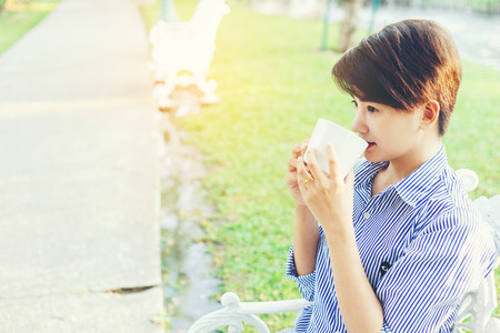 Beautiful short hair woman sitting on a white chair and drinking a favorite beverage in white cup for resting between her outdoor working business in the park. Imagens