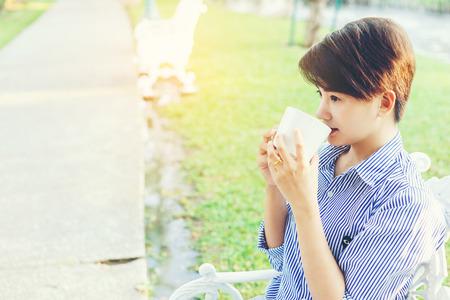 Mooie korte haarvrouwenzitting op een witte stoel en het drinken van een favoriete drank in witte kop voor het rusten tussen haar openlucht werkende zaken in het park. Stockfoto
