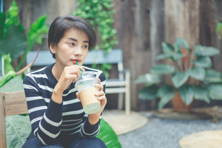 Beautiful woman in black and white sweater sitting and drinking in the garden cafe with her favorite beverage. Stock Photo