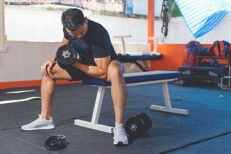 A Man using dumbbells for exercise at home gym. Imagens