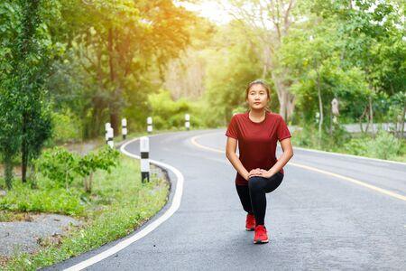 Vrouw runner's stretching haar benen spieren voordat ze gaat hardlopen. Stockfoto
