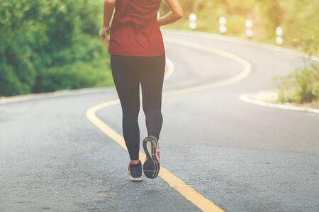 Legs of woman runner and runing at the road surround with green forest. Imagens