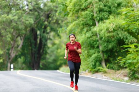 Front of woman runner and runing with full speed at the road surround with green forest.