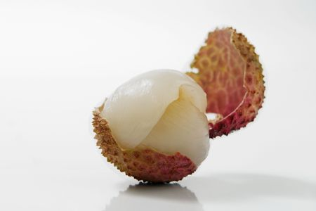litchee: close-up of an open litchi over white background
