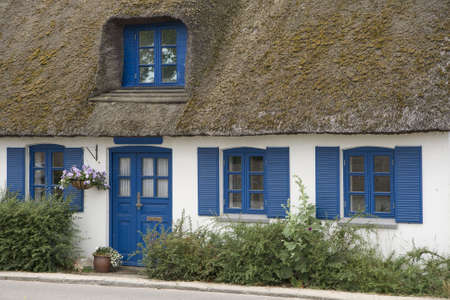 thatched roof: Cottage with thatched roof, blue door and windows Stock Photo