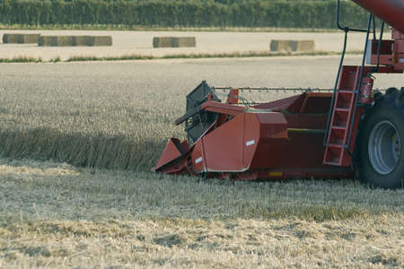 Combine harvester in a corn field with bales of straw in the background Stock Photo - 4081274