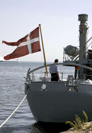 flagpoles: Navy cutter getting ready for sea in a Danish port