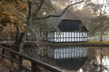 thatched roof: Small half-timbered house with thatched roof at a pond