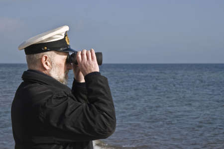 Sailor with binoculars observing the sea in calm weather