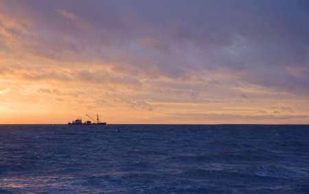 dredger: Sand-Pump Dredger in the Sunrise outside the small port Hou near Aarhus, Denmark Stock Photo