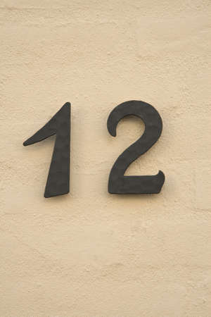 Number 12 on a yellow plastered wall