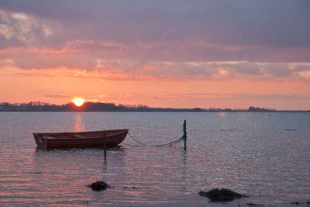 Dinghy in the sunset at Alroe near Horsens, Denmark