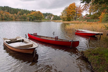 dinghies: Dinghies and a canoe in lake Almind near Silkeborg, Denmark, at fall
