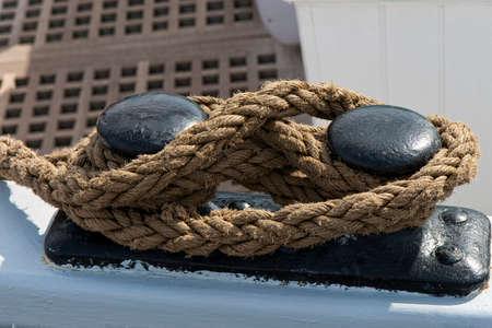 Closeup on mooring line on a mooring bitt. Shot from an old sailing ship