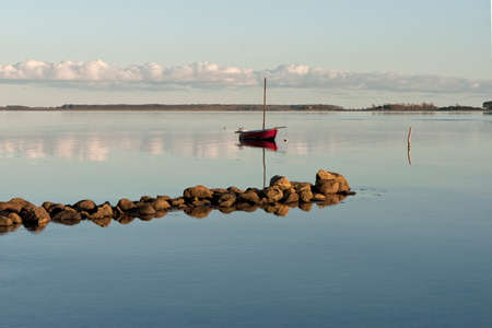 Small red sailboat at anchor at the coast in the Inlet at Horsens, Denmark Stock Photo