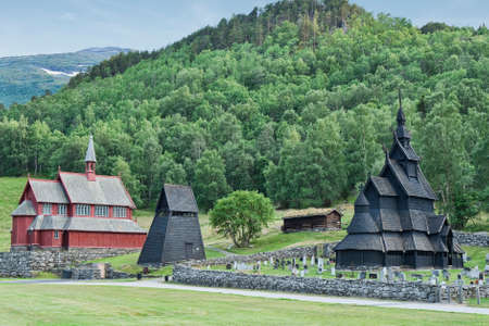 stave: Borgund, Norway 2014-07-14. Borgund Stave Church was built sometime between 1180 and 1250 AD. In the background the new church Stock Photo