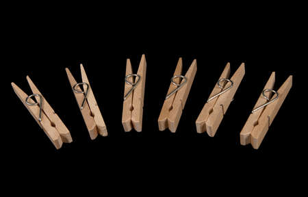 clothespegs: Closeup on wooden clothes-pegs on black background