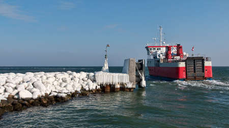 Small red and white ferry leaving port on a winter day. Stock Photo
