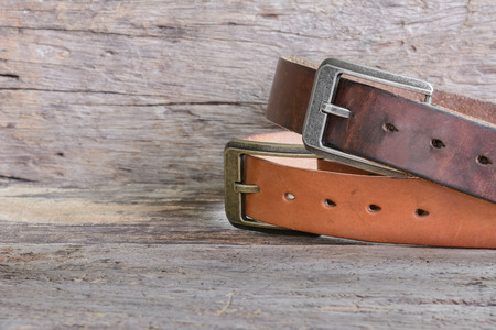 old genuine leather belt on wooden  surface with copy space for text