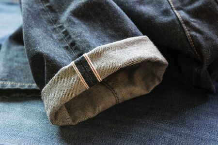 close up of fold hem red selvedge japan denim on blue jeans background
