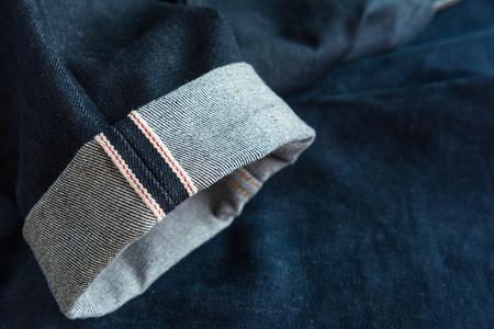fold hem of red selvedge japan dark blue jeans vintage style denim, close up Stock Photo